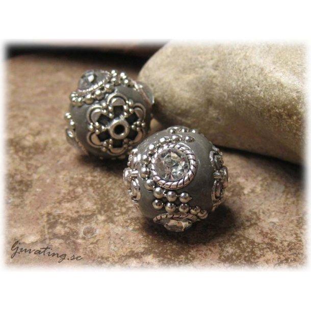 Grå pärla med metalldetaljer och clear strass