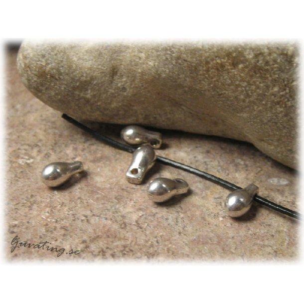 Droppe i silverfärgad metall ca 9x4,5 mm